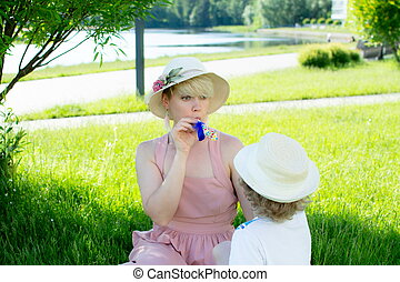 A young woman in a hat, sitting on the grass under a tree. a child is sitting next to her. They are blowing a holiday tune.