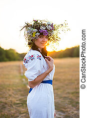 A young woman in a long white embroidered shirt and in a wreath of wild flowers stands in the field at sunset.