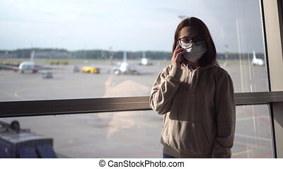 A young woman in a medical mask talks on the phone against the background of a window at the airport. Airplanes in the background.