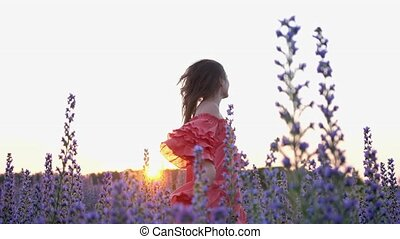 A young woman in a red dress dancing in a flower field during sunset