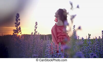 A young woman in a red dress in a flower field during sunset