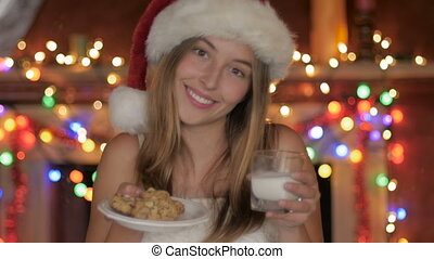 A young woman in a santa hat offers cookies and milk rack focus to cookies
