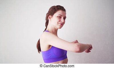 A young woman in a sports top goes in for sports at home. Sportswoman looking at the camera during a hand training slowmo