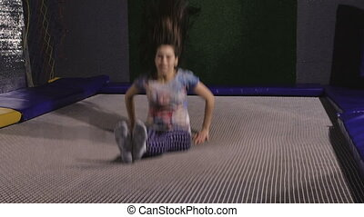 A young woman in a T-shirt. Jumping on a trampoline is...