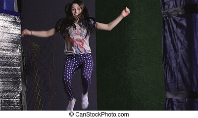 A young woman in a T-shirt. Jumping on a trampoline is ridiculous.