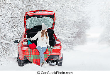A young woman in a warm sweater, hat and mittens sits on a checkered plaid in the trunk of a red car on the background of a winter forest