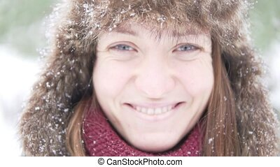A young woman in a warm winter hat is enjoying the falling snow
