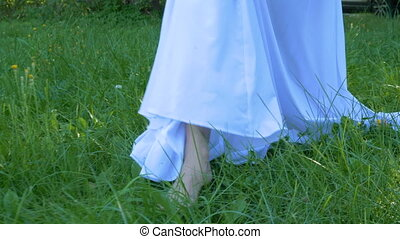 A young woman in a white dress walks on the grass barefoot. Summer day