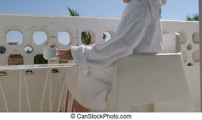 A young woman in a white robe drinking tea, coffee on the balcony.