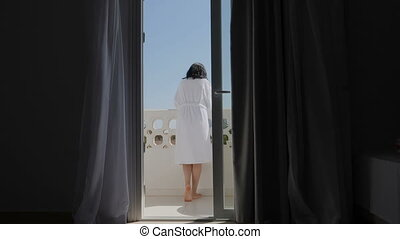 A young woman in a white robe opens the balcony door and goes out to admire the view.