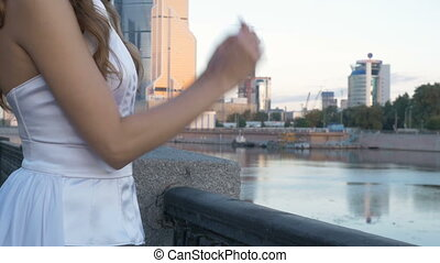 A young woman in a white suit is standing on the city embankment.