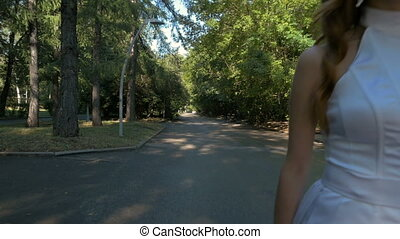 A young woman in a white suit is walking along a path in the park. Slow motion.