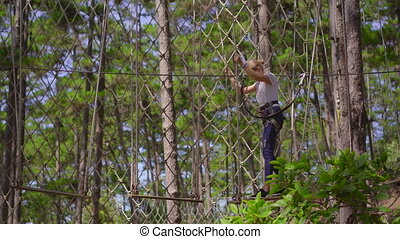 A young woman in an adventure park. She wears a safety harness. She climbs on a high rope trail. Outdoor amusement center with climbing activities consisting of zip lines and all sorts of obstacles.