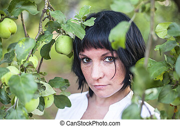 A young woman in an Apple orchard.