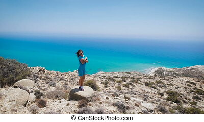 A young woman in blue dress standing on the mountain with the beautiful view to the sea