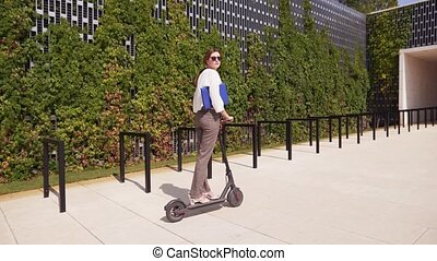 A young woman in business clothes is riding an electric scooter on a sunny summer day, tracking shot. Modern eco-friendly mobile mode of transport 4k