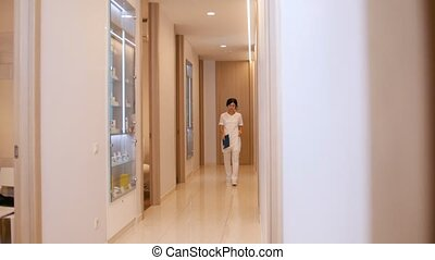 A young woman in cosmetology clinic walking on a corridor