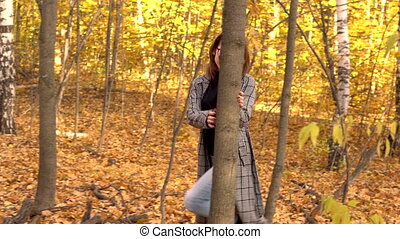 A young woman in glasses and a coat walks in the autumn forest. Yellow leaves around