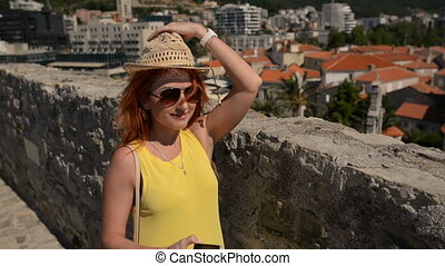 young woman in glasses and a hat makes selfie on the background of an ancient city