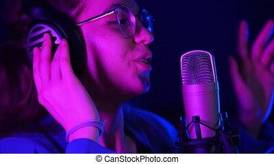 A young woman in glasses and headphones comes to the mic...