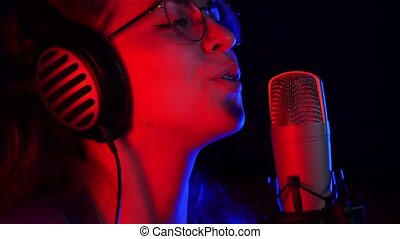 A young woman in glasses and headphones recording a song in...