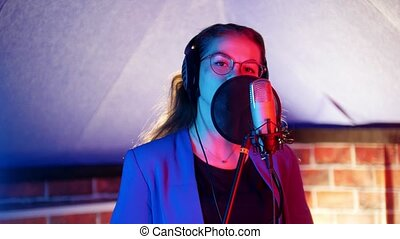 A young woman in glasses and headphones singing in the...