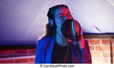 A young woman in glasses and headphones singing in the studio