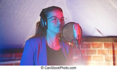 A young woman in glasses comes to a mic and puts on headphones. Mid shot