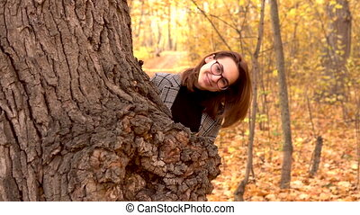 A young woman in glasses hides behind a large tree of leaves in the autumn forest. Yellow leaves around