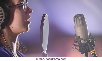 A young woman in glasses recording a song in the studio