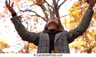 A young woman in glasses throws up yellow leaves up in the autumn forest. Slow motion