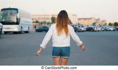 A young woman in roller-skates skating on the parking lot....