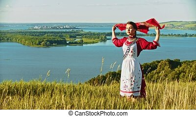 A young woman in russian folk clothes standing on the field...
