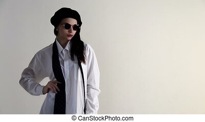 A Young woman in shirt, sunglasses and beret posing on the white background