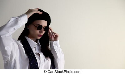 A Young woman in shirt take off the sunglasses and beret, on the white background