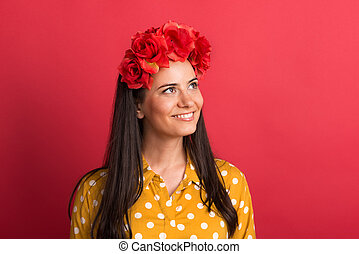 A young woman in studio with red flower headband.