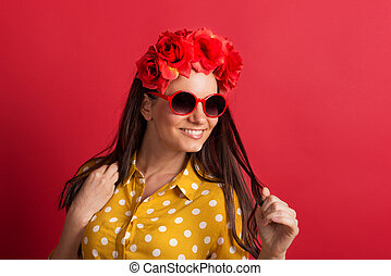 A young woman in studio with sunglasses and red flower headband.