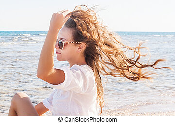 A young woman in sunglasses holds a hand to her hair fluttering in the wind near the sea. The concept of a free way of life