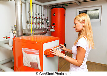 a young woman in the boiler room for heating. save energy
