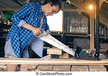 A young woman in the room sawing a Board, a carpenter's apprentice