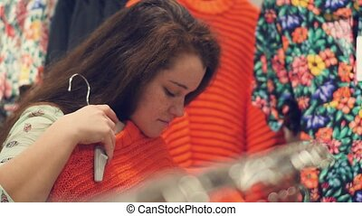 a young woman in the store choose warm winter clothes