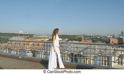 A young woman in white clothes, walking along the tourist observation platform. Beautiful panorama of the city.