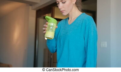 A young woman is drinking smoothies from a yellow bottle and smiling.