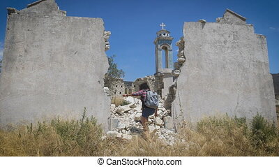 A young woman is exploring the ancient ruins of a christian...