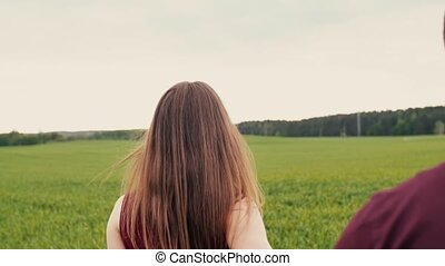 A young woman is happy with her lover, walking in a green field, taking him by the hand. Slow mo, steadicam shot