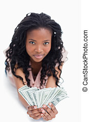 A young woman is holding American dollars in her hands