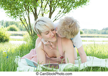A young woman is lying on the grass under a tree. a child is sitting on it. They are reading a book. a boy kisses his mother