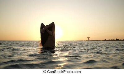 A young woman is on the sea