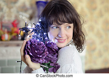 a young woman is preparing to decorate the Christmas tree