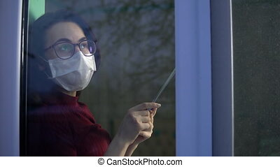 A young woman is sitting at home in quarantine with a tablet...